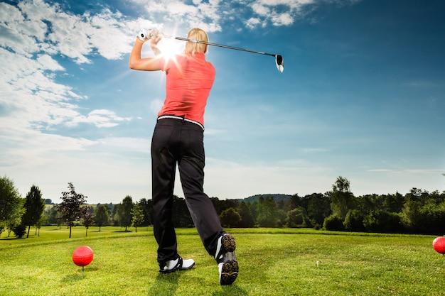 Junger golfspieler auf dem kurs, der golfschwingen tut Premium Fotos