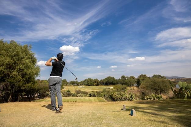Junger golfspieler, der den ball, blauen himmel schlägt Premium Fotos