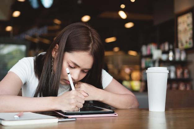 Junger grafikdesigner, der digitale tablette, notenstift und tasse kaffee auf holztisch am café verwendet. Premium Fotos