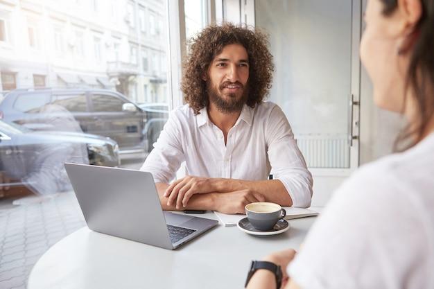 Junger gut aussehender bärtiger geschäftsmann, der termin außerhalb des büros hat, angenehmes gespräch im café beim kaffeetrinken hat, weißes hemd tragend Kostenlose Fotos