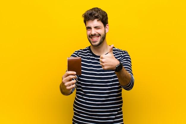 Junger gutaussehender mann auf orange Premium Fotos