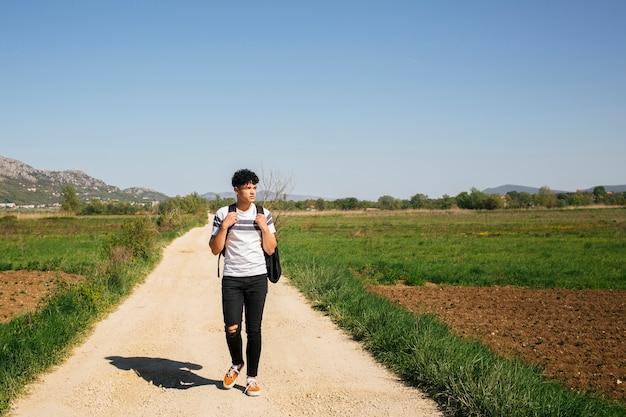 Junger gutaussehender mann, der auf tragenden rucksack des schotterwegs geht Kostenlose Fotos