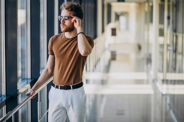 Junger gutaussehender mann, der das fenster am flughafen bereitsteht Kostenlose Fotos