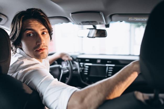 Junger gutaussehender mann, der ein auto in einem autosalon wählt Kostenlose Fotos