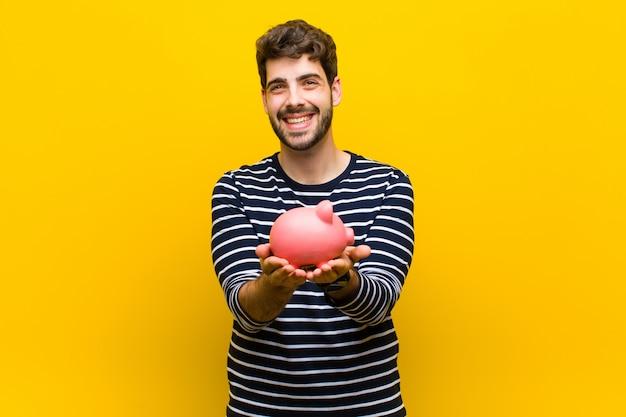 Junger gutaussehender mann, der ein sparschwein auf orange hält Premium Fotos