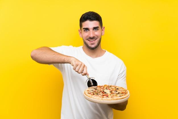 Junger gutaussehender mann, der eine pizza über lokalisierter gelber wand hält Premium Fotos