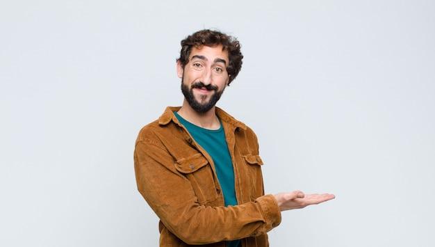 Junger gutaussehender mann, der fröhlich lächelt, sich glücklich fühlt und ein konzept im kopierraum mit handfläche gegen flache wand zeigt Premium Fotos