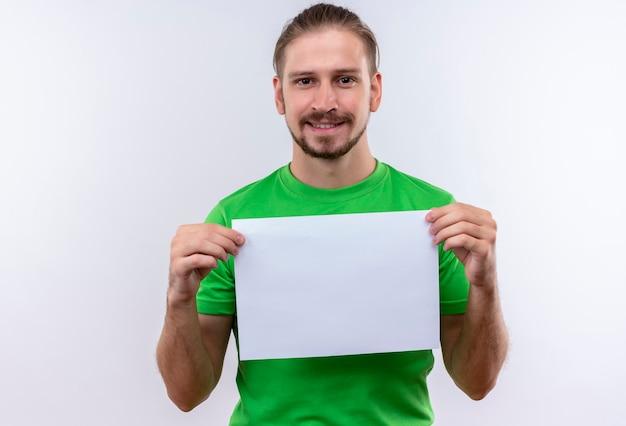 Junger gutaussehender mann, der grünes t-shirt hält, das leeres papier hält, das die kamera sieht, die zuversichtlich weiß, über weißem hintergrund steht Kostenlose Fotos