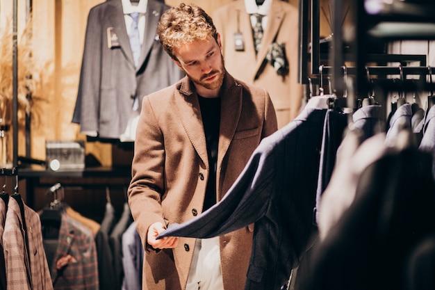 Junger gutaussehender mann, der kleidung am shop wählt Kostenlose Fotos