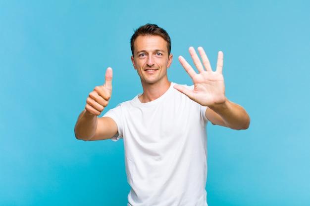 Junger gutaussehender mann, der lächelt und freundlich aussieht, nummer sechs oder sechste mit der hand vorwärts zeigend, herunterzählend Premium Fotos