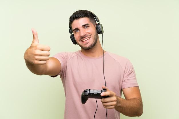 Junger gutaussehender mann, der mit einem videospielcontroller über lokalisierter grüner wand spielt Premium Fotos