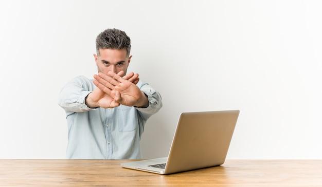 Junger gutaussehender mann, der mit seinem laptop tut eine ablehnungsgeste arbeitet Premium Fotos