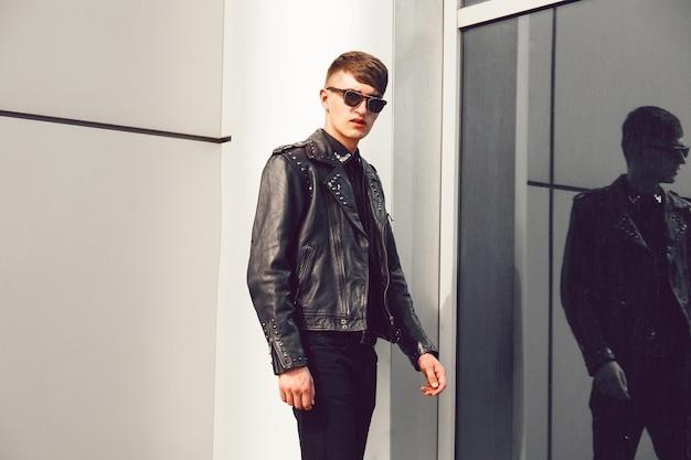 Junger gutaussehender mann, der nahe modernes geschäftszentrum aufwirft, stilvolle lederjacke mit stacheln, schwarze jeans und sonnenbrille tragend, brutaler blick. Kostenlose Fotos