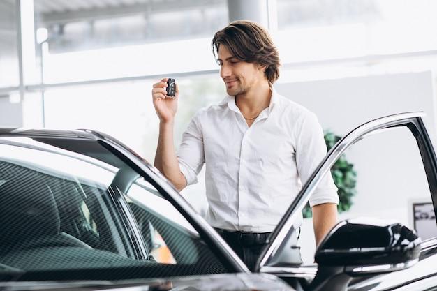 Junger gutaussehender mann, der schlüssel in einem autosalon hält Kostenlose Fotos