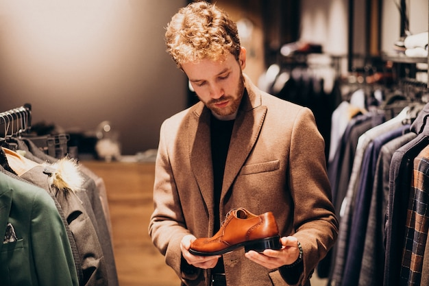 Junger gutaussehender mann, der schuhe an einem shop wählt Kostenlose Fotos