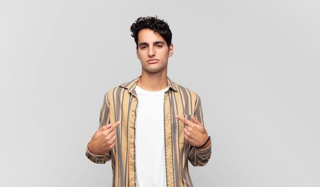 Junger gutaussehender mann, der stolz, positiv und lässig aussieht und mit beiden händen auf die brust zeigt Premium Fotos