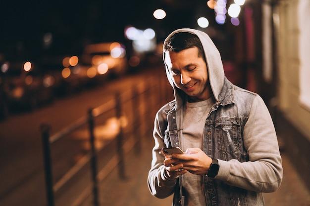 Junger gutaussehender mann, der telefon nachts in der straße verwendet Kostenlose Fotos