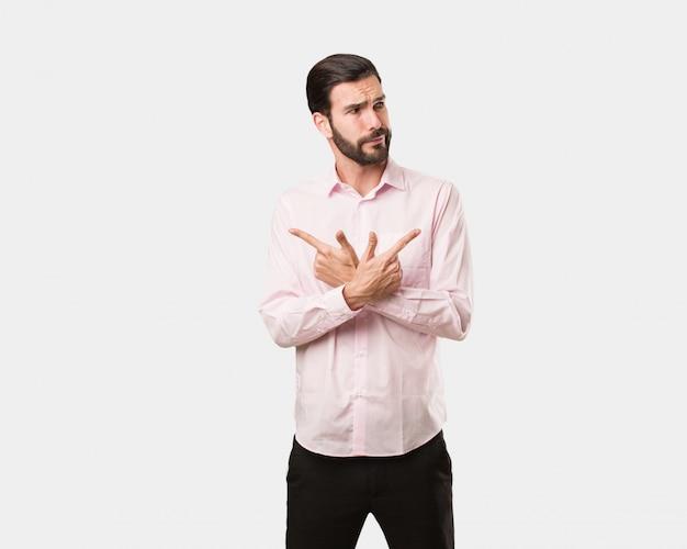 Junger gutaussehender mann entscheiden zwischen zwei optionen Premium Fotos
