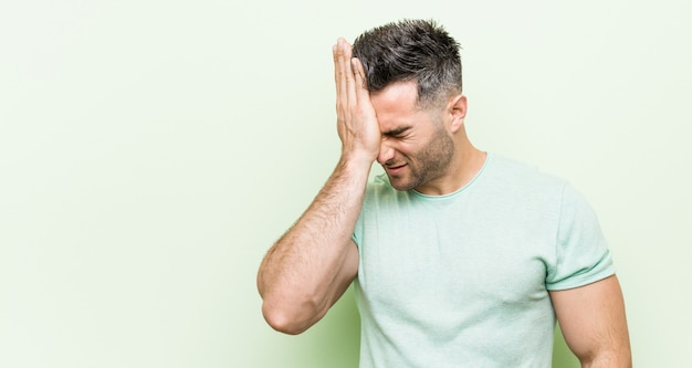 Junger gutaussehender mann gegen ein grün, das etwas vergisst, stirn mit palme schlägt und augen schließt. Premium Fotos