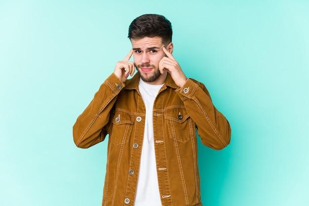 Junger gutaussehender mann konzentrierte sich auf eine aufgabe und hielt die zeigefinger, die kopf zeigen. Premium Fotos