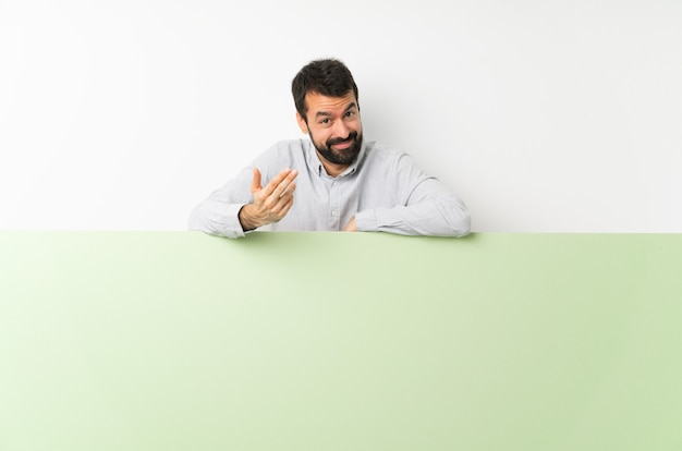 Junger gutaussehender mann mit dem bart, der ein großes grünes leeres plakat lädt ein, mit der hand zu kommen. schön, dass sie gekommen sind Premium Fotos
