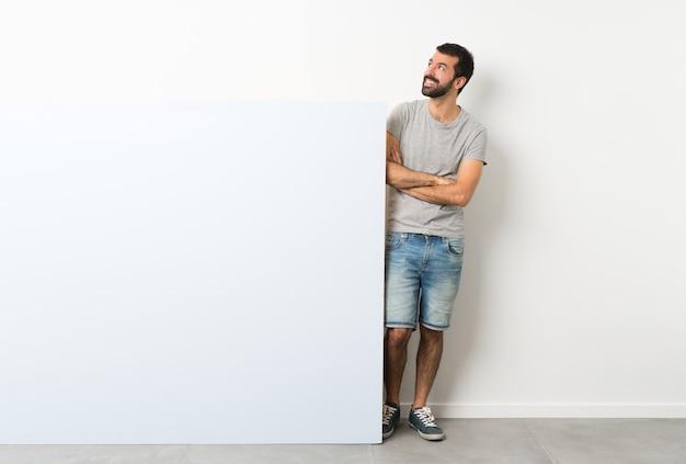 Junger gutaussehender mann mit dem bart, der ein großes leeres plakat beim lächeln oben schaut hält Premium Fotos