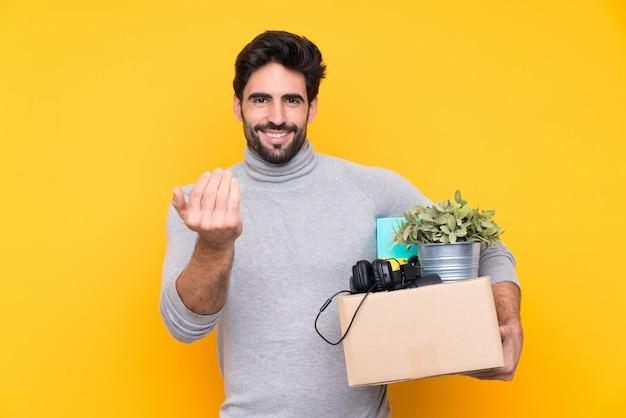 Junger gutaussehender mann mit dem bart, der eine bewegung beim einen kasten der sachen über der lokalisierten wand voll aufheben einlädt, um mit der hand zu kommen. herzlich willkommen Premium Fotos