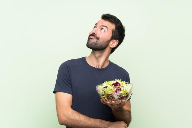 Junger gutaussehender mann mit salat über der lokalisierten grünen wand, die oben beim lächeln schaut Premium Fotos