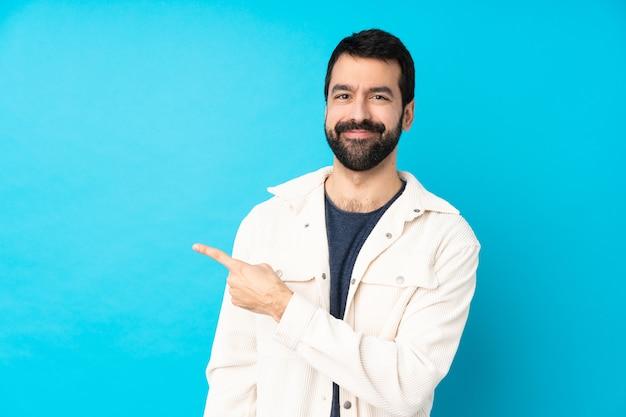 Junger gutaussehender mann mit weißer cordjacke über blau, das zur seite zeigt, um ein produkt zu präsentieren Premium Fotos