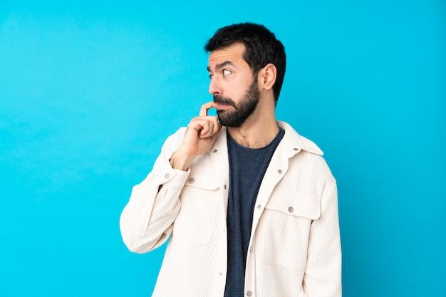 Junger gutaussehender mann mit weißer cordjacke über blau nervös und verängstigt Premium Fotos