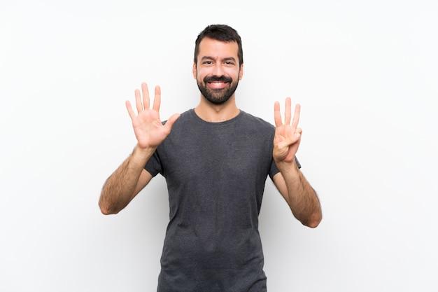 Junger gutaussehender mann über dem lokalisierten weißen hintergrund, der acht mit den fingern zählt Premium Fotos