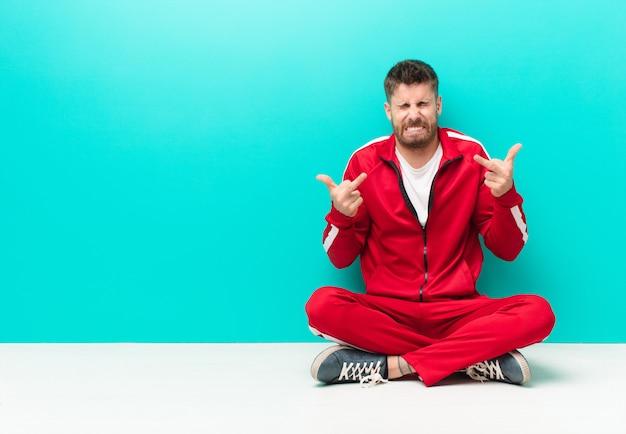 Junger handosme mann, der provozierend, konkurrenzfähig und obszön sich fühlt und den mittelfinger, mit einer rebellischen haltung gegen flache farbwand leicht schlägt Premium Fotos