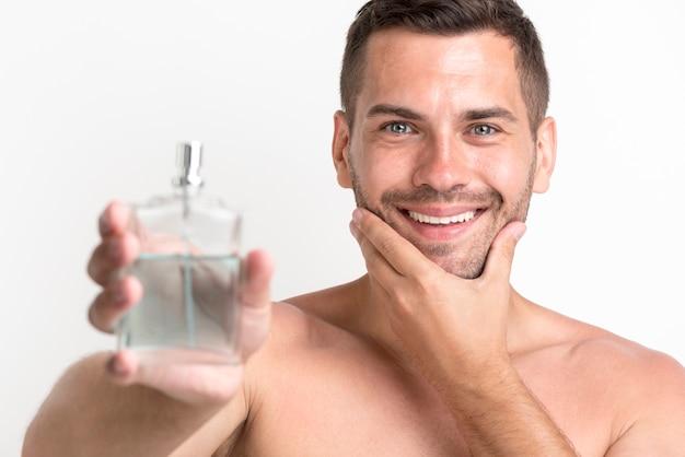 Junger hemdloser lächelnder mann, der aftershavelotionsprühflasche zeigt Kostenlose Fotos