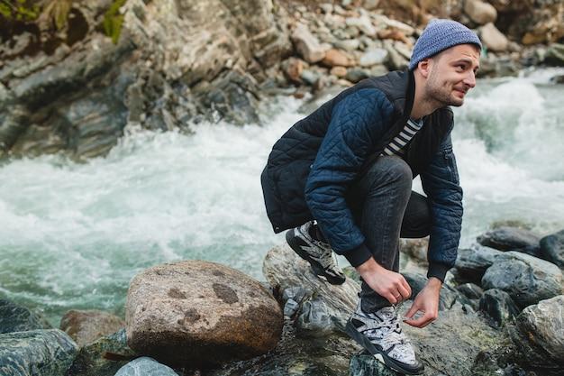 Junger hipster-mann, der auf einem felsen am fluss im winterwald geht und schnürsenkel bindet Kostenlose Fotos