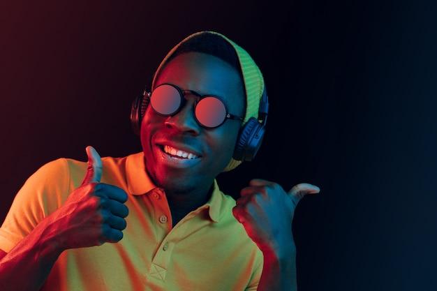 Junger hipster-mann, der musik mit kopfhörern im schwarzen studio mit neonlichtern hört. Kostenlose Fotos
