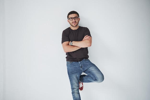 Junger hipster-typ, der eine brille trägt, die glücklich lokalisiert auf weiß lacht Kostenlose Fotos