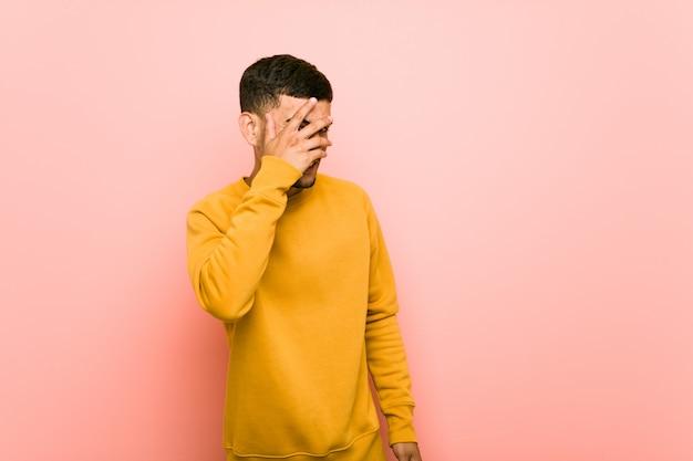Junger hispanischer mann blinzelt durch die finger, verlegenes deckgesicht. Premium Fotos