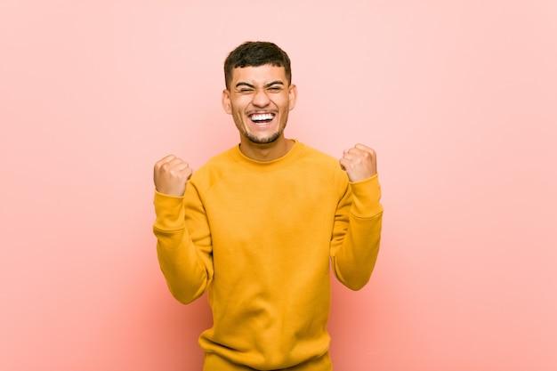 Junger hispanischer mann, der sorglos und aufgeregt zujubelt. sieg. Premium Fotos