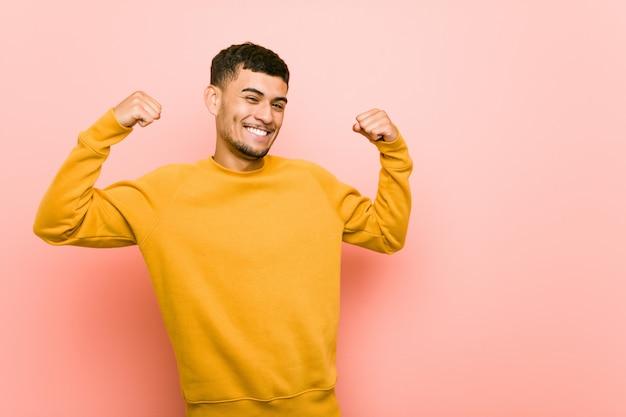 Junger hispanischer mann, der stärkegeste mit den armen, symbol der weiblichen energie zeigt Premium Fotos