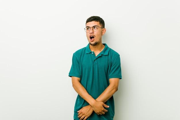 Junger hispanischer mann, der wegen etwas entsetzt ist, das sie gesehen hat. Premium Fotos
