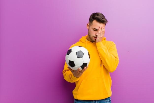 Junger hispanischer mann mit einem fußballpurpur Premium Fotos