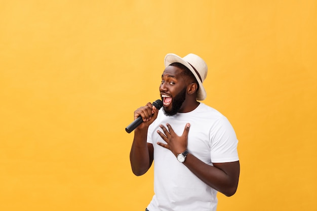 Junger hübscher afroamerikanerjunge, der emotional mit dem mikrofon lokalisiert auf gelbem hintergrund singt Premium Fotos