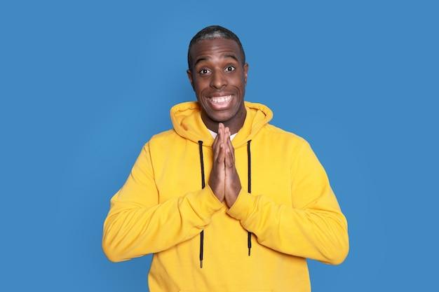 Junger hübscher afroamerikanermann, der lässigen pullover über blauem hintergrund trägt Premium Fotos