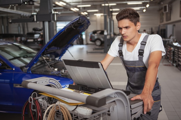 Junger hübscher automechaniker, der fahrzeug in seiner garage repariert Premium Fotos