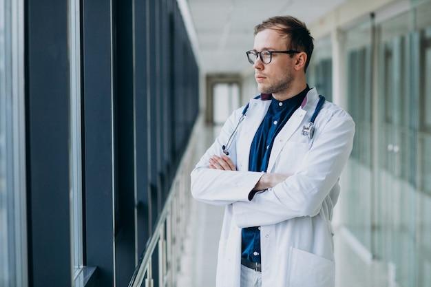 Junger hübscher doktor mit stethoskop an der klinik Kostenlose Fotos