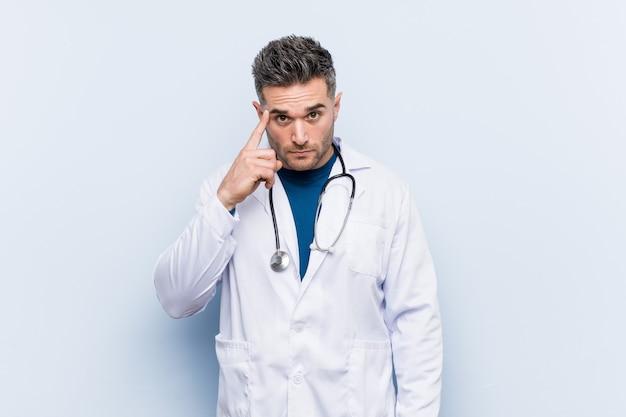 Junger hübscher doktormann, der tempel mit dem finger, denkend zeigt, konzentrierte sich auf eine aufgabe. Premium Fotos