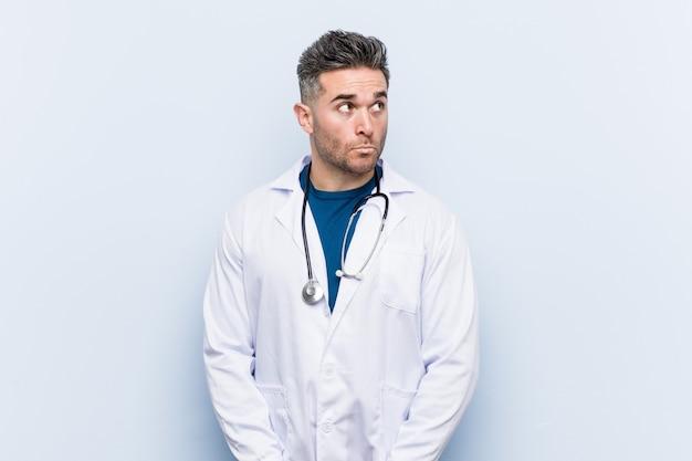 Junger hübscher doktormann verwirrt, fühlt sich zweifelhaft und unsicher. Premium Fotos