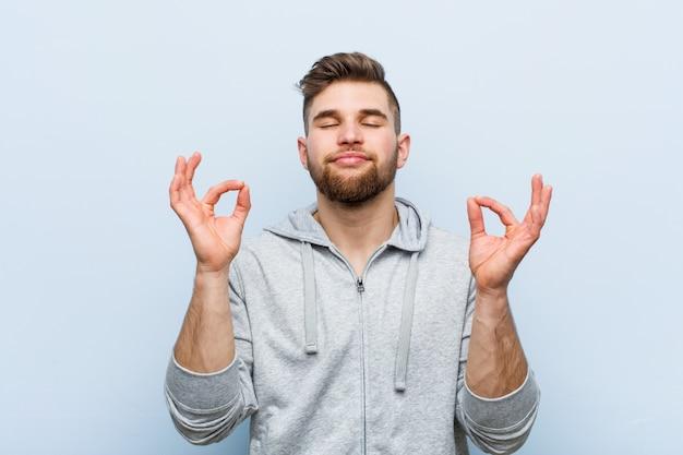 Junger hübscher eignungsmann entspannt sich nach hartem arbeitstag, er führt yoga durch. Premium Fotos