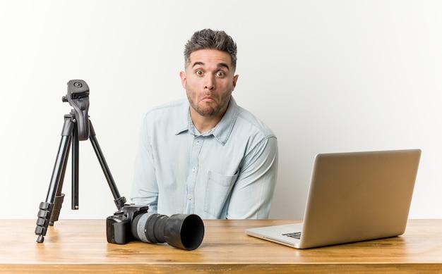Junger hübscher fotolehrer zuckt mit den schultern und die offenen augen, die verwirrt werden. Premium Fotos