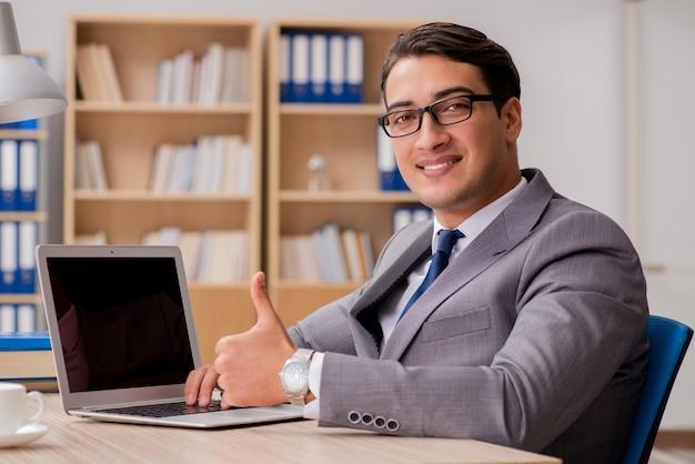 Junger hübscher geschäftsmann, der an büro arbeitet Premium Fotos